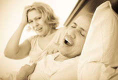 Mature  angry girlfriend cannot stand guy snoring loudly Royalty Free Stock Photo