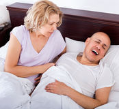 Mature  angry girlfriend cannot stand guy snoring loudly Royalty Free Stock Image