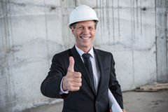 Mature architect in hardhat holding blueprint and showing thumb up stock images
