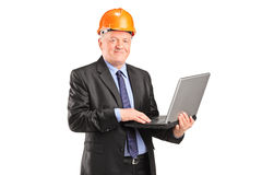 Mature architect with helmet working on a laptop Royalty Free Stock Images