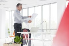 Mature architect looking at blueprint while standing in new office stock photo