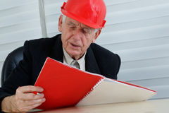 Mature architect with red helemet reading stock images