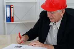 Mature architect with red helemet writing Stock Image