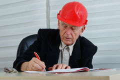 Mature architect with red helemet writing Royalty Free Stock Image