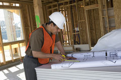 Mature Architect Working On Blueprint. At construction site Stock Images