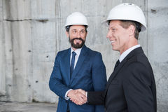 Mature architects in helmets shaking hands and smiling. Professional mature architects in helmets shaking hands and smiling Stock Photo