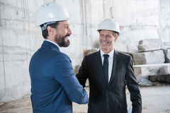 Mature architects in helmets shaking hands and smiling. Professional mature architects in helmets shaking hands and smiling Stock Images