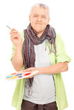 Mature artist holding a color pallet and a paintbrush. Isolated on white background stock photography