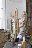 Mature Artist Painting In Art Studio Stock Image