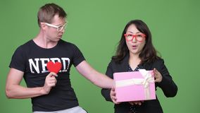 Mature Asian businesswoman and young Scandinavian nerd man celebrating Valentine`s day together. Studio shot of mature beautiful Asian businesswoman against stock footage
