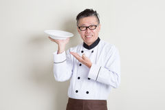 Mature Asian chef presenting dish. Portrait of 50s mature Asian male chef in uniform presenting dish and smiling, empty plate ready for food, standing on plain Stock Photography