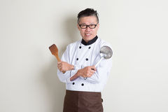 Mature Asian Chinese chef holding kitchen tools Royalty Free Stock Image