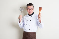 Mature Asian Chinese chef with kitchen tools. Portrait of confident 50s mature Asian male chef in uniform hands holding kitchen tools and smiling, standing on stock images