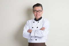 Mature Asian Chinese chef portrait. Portrait of confident 50s mature Asian male chef in uniform arms crossed, standing on plain background with shadow, copy Royalty Free Stock Images