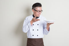 Mature Asian Chinese chef present dish Royalty Free Stock Images