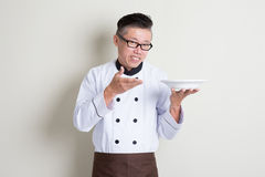 Mature Asian Chinese chef presenting dish Stock Images