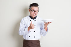 Mature Asian Chinese chef presenting dish and thumb up. Portrait of 50s mature Asian male chef in uniform presenting dish in plate and thumb up, standing on Stock Image