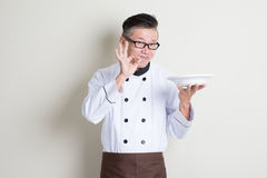 Mature Asian Chinese chef showing satisfied hand sign Stock Images