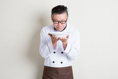 Mature Asian Chinese chef smelling aroma. Portrait of 50s mature Asian male chef in uniform presenting dish and smelling the aroma, empty plate ready for food stock photography