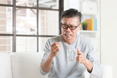 Mature Asian Chinese man eating medicine Stock Photo