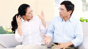 Mature Asian couple arguing. On the sofa stock video footage