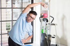 Mature Asian man arms stretching at gym. Portrait of active 50s mature Asian man in sportswear doing arms stretching exercise, workout at indoor gym room stock photography