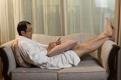 Mature Asian man in bathrobe Stock Images