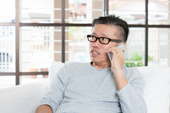 Mature Asian man calling on smartphone. Modern technology, age and people concept. Mature Asian man using smart phone. Living lifestyle at home Stock Images