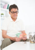 Mature Asian man counting money. Portrait of mature Asian man counting on his savings, sitting on sofa at home, senior retiree indoors living lifestyle Stock Photo