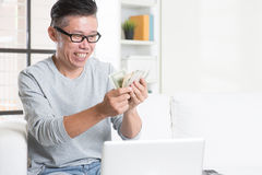 Mature Asian man counting money Royalty Free Stock Image