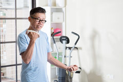 Mature Asian man with dumbbells at gym Royalty Free Stock Photography
