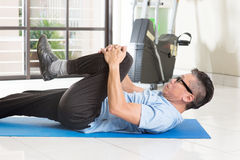 Mature Asian man exercise at gym. Portrait of active 50s mature Asian man in sportswear doing leg stretching on exercise mat, workout at indoor gym room stock photos