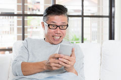 Mature Asian man getting excited while using smartphone Stock Photography