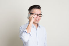 Mature Asian man making call on smart phone Royalty Free Stock Images