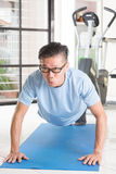 Mature Asian man pushup at gym. Portrait of active 50s mature Asian man in sportswear doing pushup on exercise mat, workout at indoor gym room royalty free stock photos