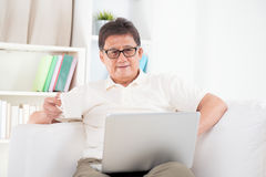 Mature Asian man surfing internet Stock Photo