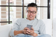 Mature Asian man texting on smartphone Royalty Free Stock Photo