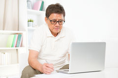 Mature Asian man using computer. Portrait of mature Asian man using computer laptop and writing something on paper, sitting on sofa at home, senior retiree royalty free stock image