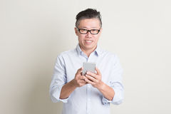 Mature Asian man using smart phone Royalty Free Stock Image