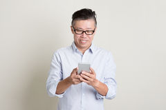 Mature Asian man using smartphone Royalty Free Stock Photo