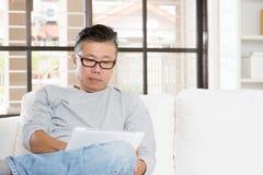 Mature Asian man using tablet computer Stock Image
