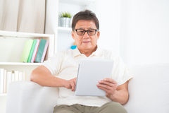 Mature Asian man using tablet pc. Portrait of mature Asian man using tablet pc, sitting on sofa at home, senior retiree indoors living lifestyle Stock Images