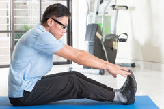 Mature Asian man workout at gym. Portrait of 50s mature Asian man in sportswear doing leg stretching on exercise mat, workout at indoor gym room stock photography