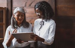Mature Asian Woman And Young African Businesswomen Working Together While Standing Next To Wooden Office Wall. Two Women Royalty Free Stock Photography