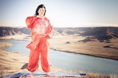 Mature asian woman doing kundalini yoga. Mature asian woman doing kundalini or Zhan zhuang Qigong yoga. Kundalini is term for spiritual energy, life force Stock Photo