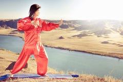Mature asian woman doing kundalini yoga. Mature asian woman doing kundalini or Zhan zhuang Qigong yoga. Kundalini is term for spiritual energy, life force Royalty Free Stock Images