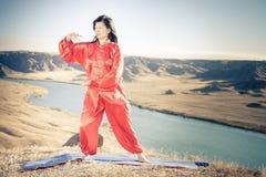 Mature asian woman doing kundalini yoga. Mature asian woman doing kundalini or Zhan zhuang Qigong yoga. Kundalini is term for spiritual energy, life force Royalty Free Stock Photo