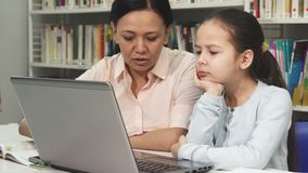 Mature Asian woman helping her tired daughter with homework