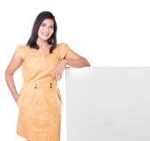Mature Asian woman presenting a blank white billboard Stock Photo