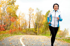 Mature Asian woman running active in her 50s. Middle aged female jogging outdoor living healthy lifestyle in beautiful autumn city park in colorful fall Royalty Free Stock Photos